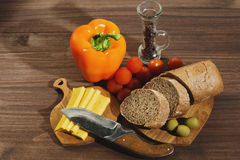 Different ingridients suitable for mediterranean cuisine. Brown bread and yellow cheese and some vegetables like bell pepper, tomatoes and pickled olives Royalty Free Stock Images