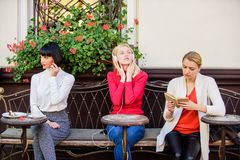 Different interests. Group pretty women cafe terrace entertain themselves with reading speaking and listening stock photo