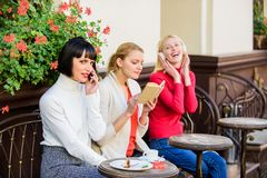 Different interests. Hobby and leisure. Group pretty women cafe terrace entertain themselves with reading speaking and royalty free stock photos