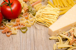 Different italian pasta, pecorino and red tomato Stock Photos
