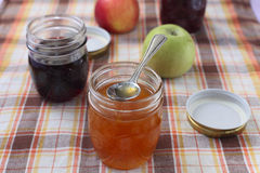 Different jams. Several glass cans with different jams and apples, orange jam closeup with a spoon Royalty Free Stock Image