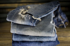 Different jeans folded on a wooden background. Pile of Old Indigo Jeans Denim on Wooden Table Background Texture Royalty Free Stock Images