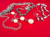 Different Jewelry. Necklaces, pearls, earrings on the red background Royalty Free Stock Image