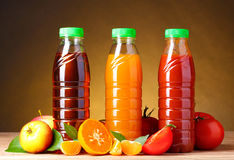 Different juices and fruits on. Wooden table on brown background stock photography