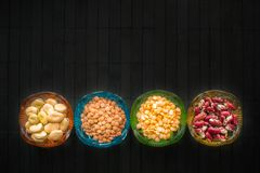 Different kind of beans and lentils in colored glass dishes on b royalty free stock photo