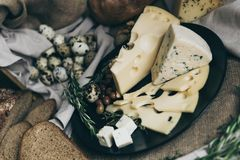 Different kind of cheese - blue cheese, cheese with holes, cheese slices and cubes on black plate. Slices and whole royalty free stock images