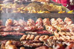 Different kind on grilled meat, sausages and fried potatoes with smoke Stock Images