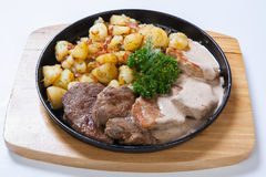 Different kind of meat with potatoes on a grill pan royalty free stock photography
