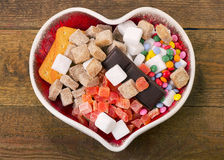 Different kind of sugar, candies and cookies in heart shaped bow Stock Image