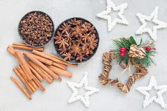 Different kinds of aromatic winter spices in bowls and on table, christmas decoration on a gray concrete background, horizontal Stock Image