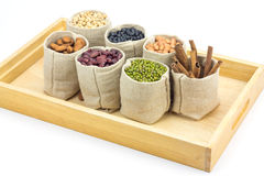 Different kinds of beans and cinnamon in sacks bag on wooden tray Royalty Free Stock Photo