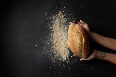 Different kinds of bread on background. Baking and cooking concept background. Someone holding fresh break over black background. Grain bread with flour Royalty Free Stock Photo