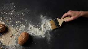 Different kinds of bread on background. Someone sweeping flour with brush over black background. Several buns represented on table. Cooking process concept Royalty Free Stock Photo