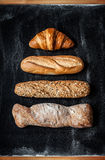 Different kinds of bread rolls on black from above stock photo