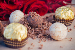 Different kinds of candies covered by chocolate near rose flower. Different kinds of chocolate truffle candies covered by grated chocolate over craft paper near Stock Image