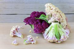 Different kinds of cauliflower lay on a wooden table. Stock Images