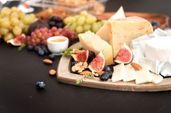 different kinds of cheeses, honey, figs, nuts, grapes, and fruit on a table. Selective focus. Copy space. royalty free stock photography