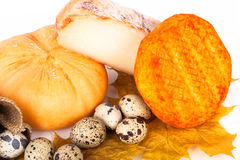Different kinds of cheeses and quail eggs with leafs on light ba Stock Image
