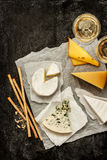 Different kinds of cheeses, white wine and snacks on black Stock Photo