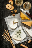 Different kinds of cheeses, white wine and snacks on black Stock Photography