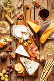 Different kinds of cheeses, wine, baguette, fruits and snacks stock image