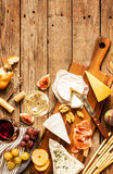 Different kinds of cheeses, wine, baguettes, fruits and snacks Royalty Free Stock Photos