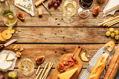 Different kinds of cheeses, wine, baguettes, fruits and snacks Royalty Free Stock Images