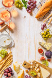 Different kinds of cheeses, wine, baguettes and fruits on white Stock Images