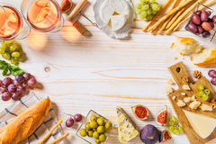 Different kinds of cheeses, wine, baguettes and fruits on white Stock Photo