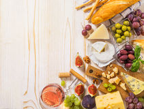 Different kinds of cheeses, wine, and snacks on the white wood Royalty Free Stock Photos
