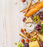 Different kinds of cheeses, wine, and snacks on the white wood Royalty Free Stock Image