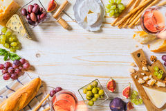 Different kinds of cheeses, wine, and snacks on the white wooden Stock Photo