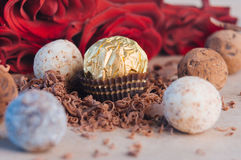 Different kinds of chocolate truffle candies near rose flowers. Different kinds of chocolate truffle candies covered by grated chocolate over craft paper near Stock Image
