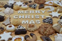 Christmas cookies and MERRY CHRISTMAS. Different kinds of Christmas cookies on a breadboard around the words: MERRY CHRISTMAS Stock Image
