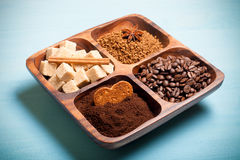 Different kinds of coffee on wooden plate on blue table. Toned Stock Photo