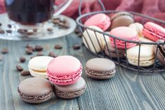 Different kinds of colorful french dessert macaron with different fillings on table, served with coffee, horizontal Stock Photo