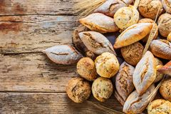 Different kinds of fresh bread on wooden table. assortment of bread on brown background. Different kinds of fresh bread on wooden table. assortment of bread on stock photo