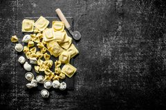 Different kinds of Italian raw pasta. On dark rustic background royalty free stock image