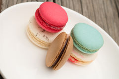 Different kinds of macaroon on white plate. And wooden table Royalty Free Stock Images