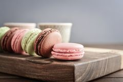 Different kinds of macaroons. In row with tea cups on wooden background closeup Royalty Free Stock Photo