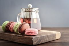 Different kinds of macaroons. In row with teapot on wooden background closeup Stock Photography