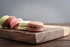 Different kinds of macaroons. In row on wooden background closeup Stock Photo