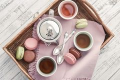Different kinds of macaroons with glass teapot. And cups on rattan tray top view stock photography