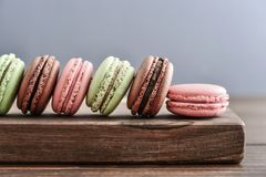 Different kinds of macaroons. In row  on blue background closeup Royalty Free Stock Photo