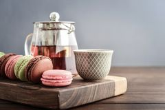 Different kinds of macaroons. In row with teapot on wooden background closeup Stock Photo
