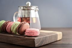 Different kinds of macaroons. In row with teapot on wooden background closeup Royalty Free Stock Images