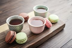 Different kinds of macaroons. With tea cups on wooden  background closeup Stock Image