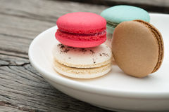 Different kinds of macaroons on white plate. And wooden table Royalty Free Stock Images