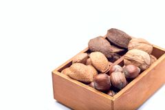 Different kinds of nuts in the shell: hazelnut, walnut, almond and brazil nuts in wooden box, isolated on a white background. Different kinds of nuts in the stock photos