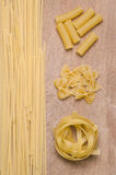 Different kinds of pasta. On a wood cutting board Stock Photography